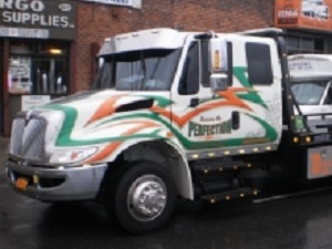 white tow truck with orange and green detailing