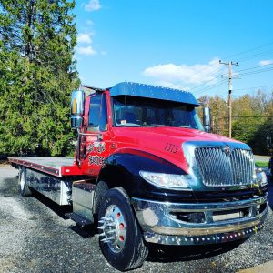 red flatbed tow truck with lighted visor and chrome bumper